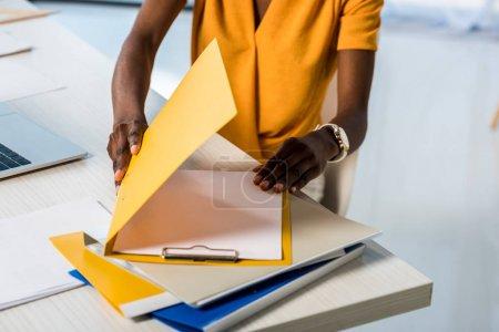 photo recadrée d'afro-américaine avec dossiers distants de travailler à la maison bureau
