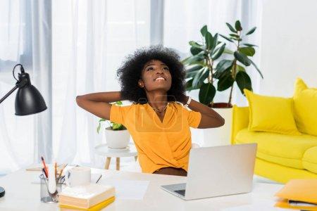 Photo pour Portrait d'une femme afro-américaine souriante assise à table avec un ordinateur portable à la maison - image libre de droit