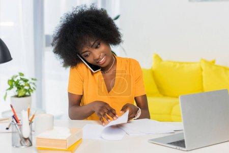 Photo pour Portrait de souriant pigiste afro-américaine parler sur smartphone tout en travaillant à la maison - image libre de droit