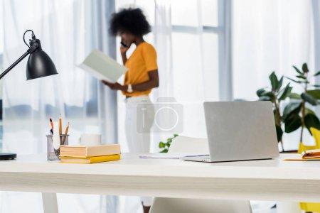 Photo pour Foyer sélectif de l'ordinateur portable sur le lieu de travail et afro-américain pigiste parler sur smartphone sur fond à la maison - image libre de droit