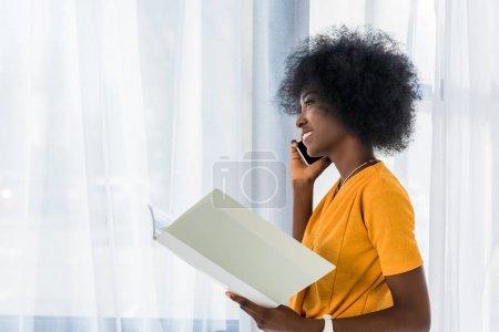 Photo pour Vue latérale du pigiste afro-américain avec dossier parlant sur smartphone à la maison - image libre de droit