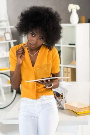 pensive african american freelancer with notebook at workplace at home office