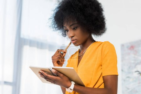 portrait of thoughtful african american freelancer with notebook at home office