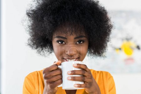 portrait of smiling african american woman with cup of coffee at home