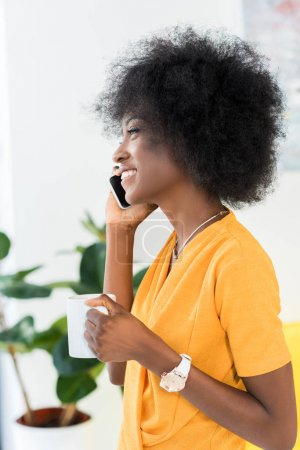 side view of smiling african american with cup of coffee talking on smartphone at home