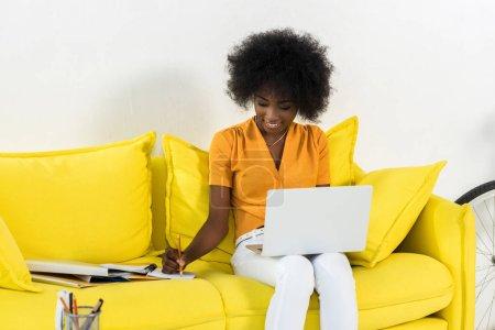 Photo pour Sourire pigiste femelle afro-américaine avec ordinateur portable, prendre des notes tout en travaillant sur le sofa à la maison - image libre de droit
