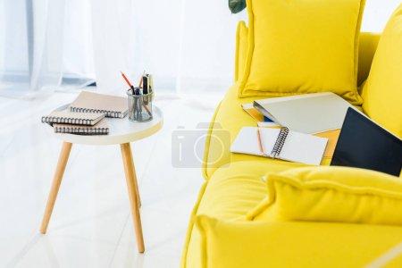 Photo pour Vue rapprochée de l'ordinateur portable, des ordinateurs portables et des dossiers sur canapé jaune au bureau à la maison - image libre de droit