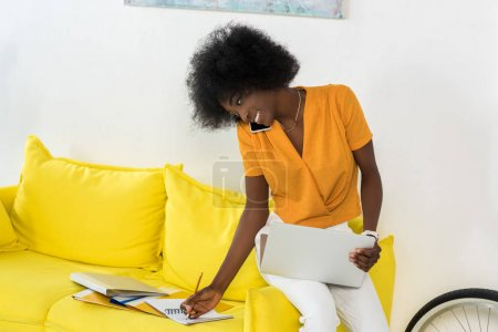 smiling african american female freelancer with laptop talking on smartphone while working on sofa at home