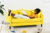 side view of african american woman with papers remote working on sofa at home