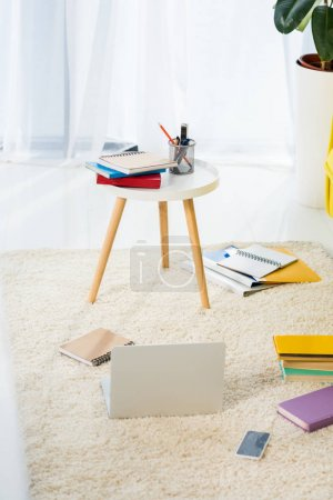close up view of laptop, notebooks and folders arranged on floor at home office