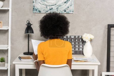 back view of african american freelancer at workplace at home office