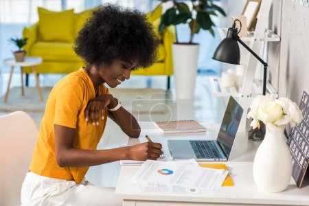 Photo for Side view of smiling african american female freelancer working at home - Royalty Free Image