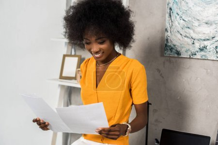 portrait of smiling african american freelancer with papers at home office