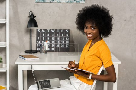 Photo for Side view of smiling african american woman with notebook and laptop sitting at table at home office - Royalty Free Image