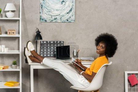 Photo pour Sourire femme afro-américaine avec ordinateur portable assis à table avec ordinateur portable à la maison, Bureau - image libre de droit