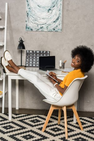 smiling african american woman with notebook sitting at table with laptop at home office