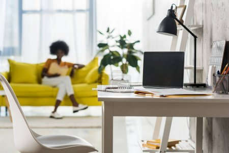 selective focus of laptop on table and african american freelancer at home office