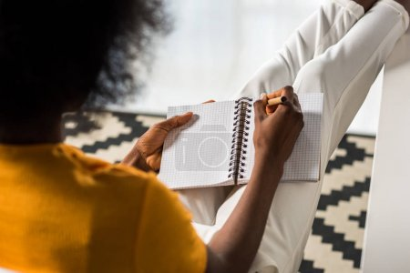 partial view of african american freelancer making notes in notebook at home office