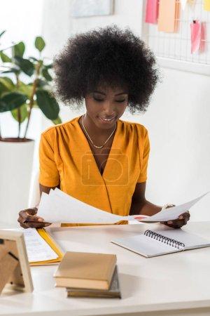 Photo pour Portrait de sourire afro-américaine freelance avec papiers sur lieu de travail à la maison bureau - image libre de droit