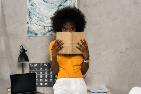 obscured view of african american woman covering face with notebook in hands at home office