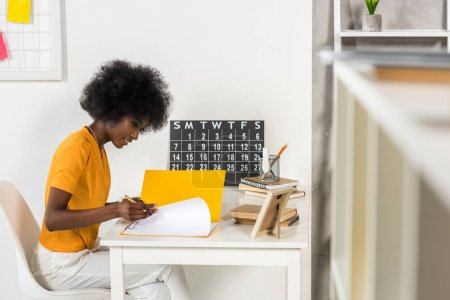 smiling african american freelancer with papers at workplace at home office
