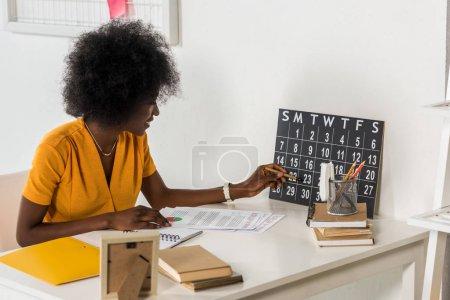 Photo pour Jeune freelance afro-américain vérifier calendrier sur le lieu de travail au bureau à domicile - image libre de droit