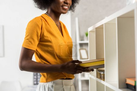 partial view of smiling african american woman with books at home