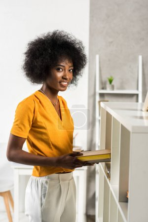 side view of smiling african american woman with books at home