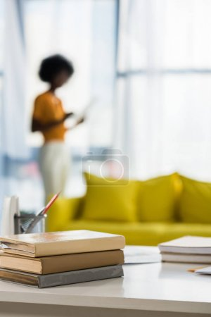 selective focus of books at workplace and african american freelancer on background at home office