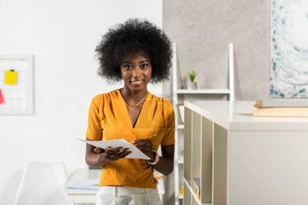 Photo pour Portrait de souriant afro-américain pigiste avec des papiers au bureau à domicile - image libre de droit