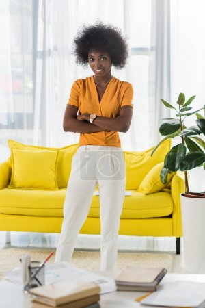 smiling african american freelancer with arms crossed standing at home office