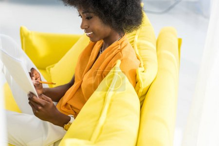 side view of smiling african american woman with papers remote working on sofa at home