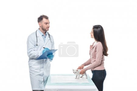 young woman with kitten on table and male veterinarian writing in clipboard isolated on white background