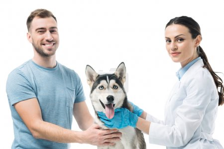smiling young man with husky and female veterinarian isolated on white background