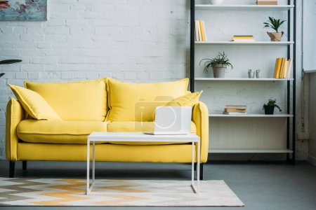 Photo for Laptop on table near yellow sofa in living room - Royalty Free Image