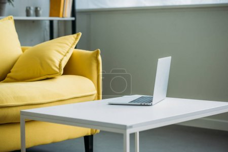 laptop on table near yellow sofa in living room