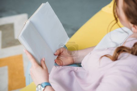 cropped image of woman reading book on sofa at home