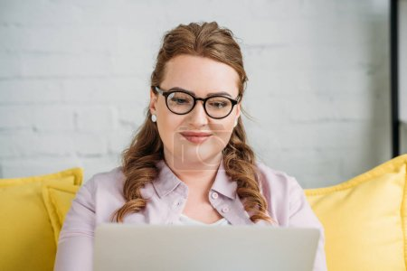 beautiful freelancer sitting with laptop on sofa at home