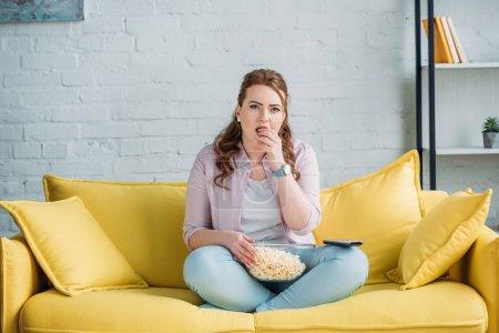 Photo pour Belle femme regarder film et manger des pop-corn à la maison - image libre de droit