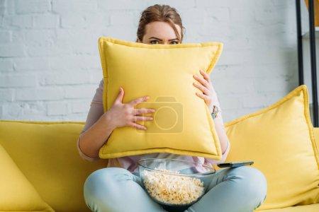 Photo pour Femme à l'affût de coussin tout en regardant le film d'horreur avec pop-corn à la maison - image libre de droit