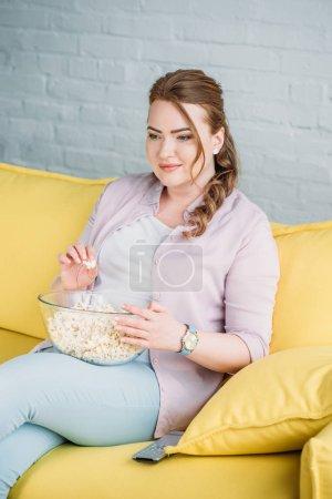 Photo pour Jolie femme regarder film avec pop-corn à la maison - image libre de droit