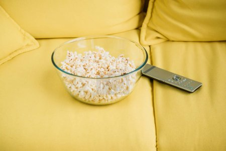 glass bowl with popcorn and remote control on yellow sofa