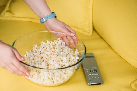 cropped image of woman putting bowl with popcorn on sofa at home