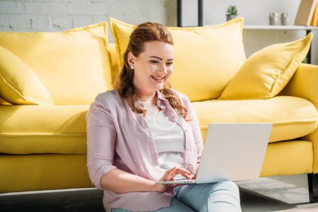 smiling beautiful woman sitting on floor and using laptop at home