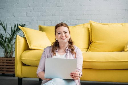 smiling beautiful woman holding laptop and looking at camera at home