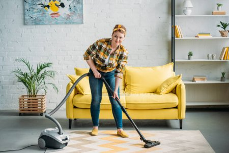beautiful woman cleaning carpet with vacuum cleaner at home