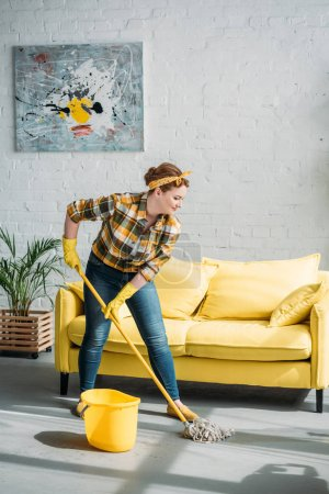 beautiful woman cleaning floor with mop at home