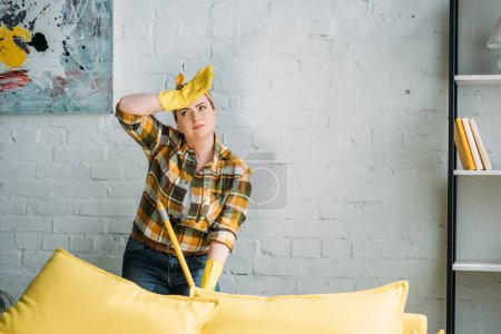 tired woman cleaning apartment with mop