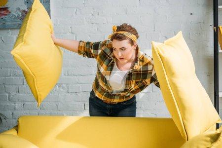 Photo pour Belle femme regardant sous les coussins jaunes à la maison - image libre de droit
