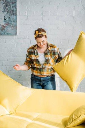 Photo pour Belle femme tenant coussin jaune à la maison - image libre de droit